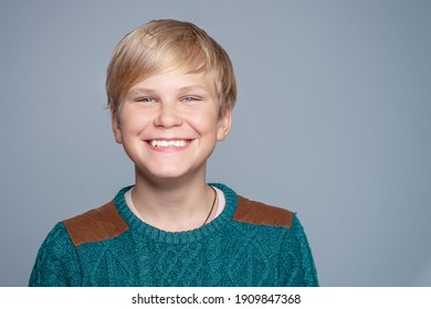 Handsome child with a beaming smile. Blond teen boy 12-14 year old over gray background.