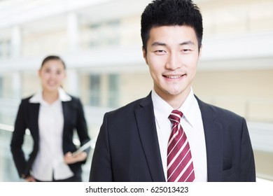 handsome chinese businessman and pretty chinese businesswoman with digital tablet in modern office