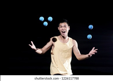 Handsome Chinese guy juggling blue balls on black background. Emotional juggler.