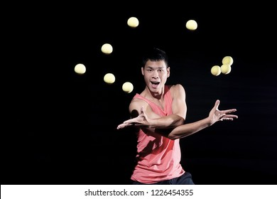 Handsome Chinese man juggling yellow balls on black background. Emotional juggler.