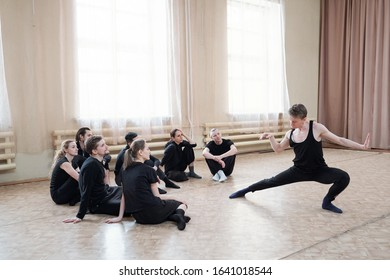 Handsome choreographer demonstrating contemporary dance moves to his young team