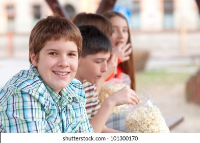 Handsome chubby teenager spending time with his friends outdoor.