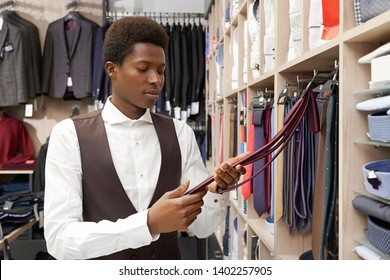Handsome client of shop choosing necktie. African man holding red cravat looking at it. Young man wearing in white shirt and black waistcoat. Huge choice of clothing for men.