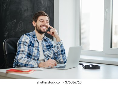 Handsome college student using his laptop computer in the study room
