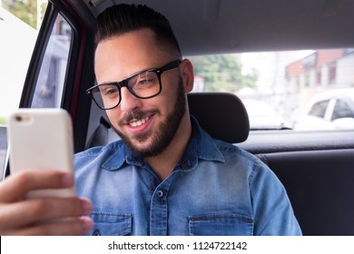 Handsome commuter student man with glasses on smartphone using app texting sms message in back seat of car. Concept of commute, mobility, connection, aspirations.