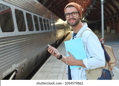 Handsome commuter using the phone while waiting for his train