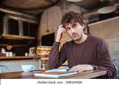 Handsome concentrated attractive curly young man writing notes in notebook and planning his schedule sitting in cafe at the wooden table