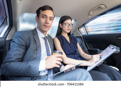 Handsome confident businessman and associates traveling, working on laptop discussing  for business strategy chart graph while sit in the luxury car on the back seat  to a meeting.In selective focus.