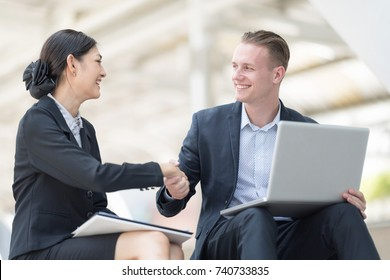 Handsome and Confident Businessman Using Laptop Computer outdoor Discussing With Beautiful Business Partner While sitting on Stairs Way against Blurred City Center Lifestyle Concept.