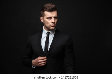 Handsome confident businessman wearing suit standing isolated over black background, posing