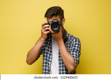 Handsome and confident indian man photographer with a large professional camera taking pictures photo shooting on the on the yellow background.