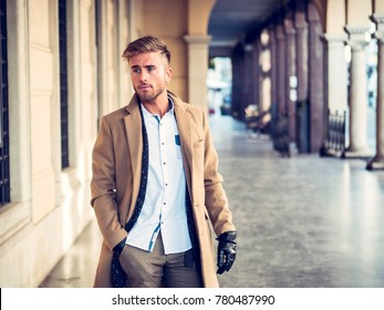 Handsome confident male model in elegant coat and gloves standing on background of exterior gallery.