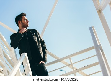 Handsome confident man with beard posing outside