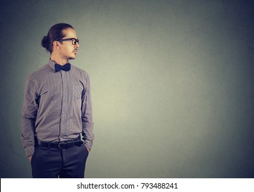 Handsome confident man in bow-tie and eyeglasses standing with hands in pockets looking away.