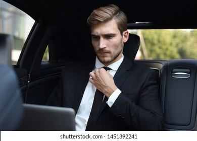 Handsome confident man in full suit straightens tie while working on laptop and sitting in the car.
