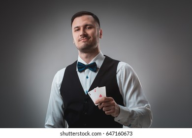 Handsome confident man holding cards looking at camera.