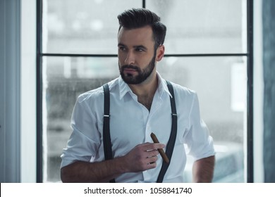 Handsome confident man is holding a cigar and looking away while sitting near the window