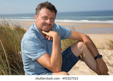 Handsome and confident man smiling and sitting at the beach