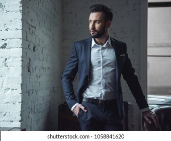 Handsome confident man in suit is holding one hand in pocket and looking away while standing indoors