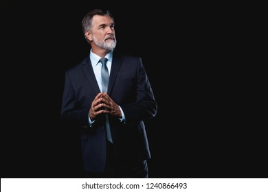 Handsome confident mature business man isolated on black background