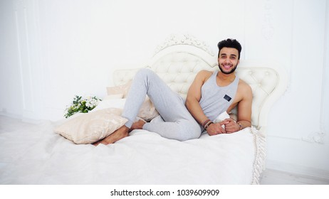 Handsome and Confident Nice Muslim Man in Bed With Knees Bent Legs, Looking at Camera Smiling Showing Thumbs up Gesture on Big, Soft Bed in Bright and Spacious Bedroom With Flowers in Pots. Arab Guy
