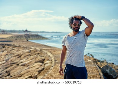 Handsome and confident. Outdoor portrait of happy young african man on the beach.
