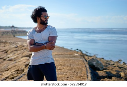 Handsome and confident. Outdoor portrait of young african man on the beach.