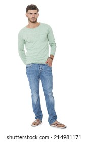 Handsome confident relaxed handsome young man with a beard posing with his hands in his pockets in jeans and slip slops, isolated on white