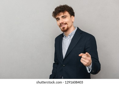Handsome confident young businessman wearing a jacket standing isolated over gray background, pointing finger at camera