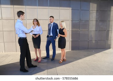 Handsome confident young male guy, businessman, student holds tablet in hands and deliver presentations, talks about gadget, advertises new technology to colleagues who listening to attentively, and