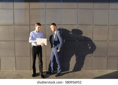 Handsome confident young male man, businessman, student holds laptop in hands and deliver presentations, talks about gadget, advertises new technology to colleague who listening to attentively, and