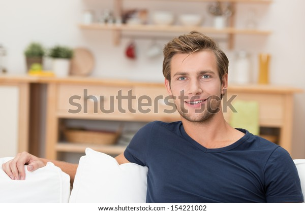 Handsome confident young man relaxing at home on the sofa looking at the camera with a friendly smile