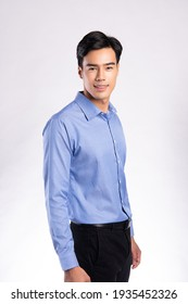 handsome confident young man standing and smiling in a blue shirt. on white background.
