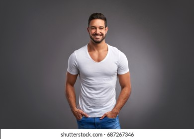 A handsome confident young man standing and smiling in a white t-shirt