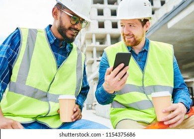 Handsome construction engineer with cup of hot beverage smiling and showing smartphone to young colleague while relaxing during break on construction site