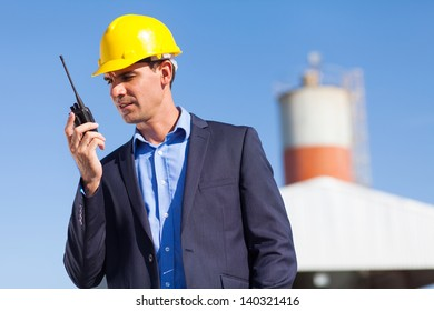 handsome construction manager using walkie talkie outdoors