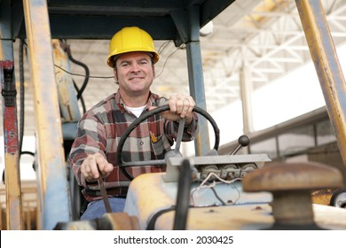 A handsome construction worker driving a bulldozer on a construction site.
