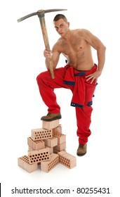 Handsome construction worker with a pickaxe and bricks over white background