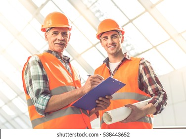 Handsome construction workers in protective helmets and vests are studying documents in the office center