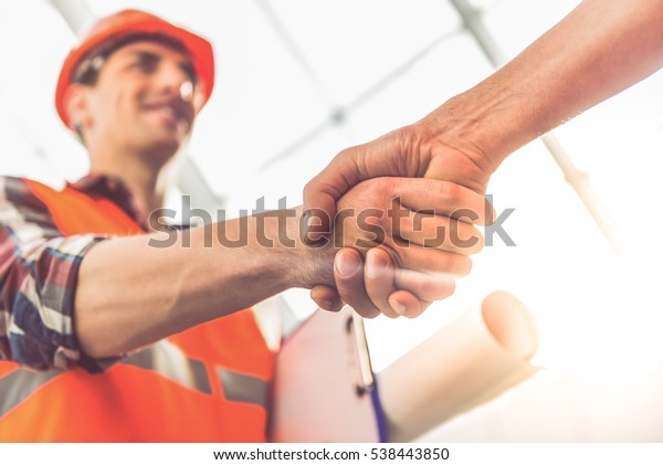 Handsome construction workers in protective helmets and vests are shaking hands while working in the office center