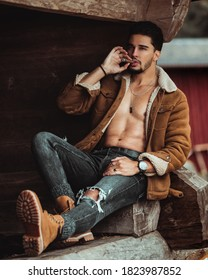 handsome countryside male model smoking a cigar and cutting wood in his farm in Stockholm Sweden