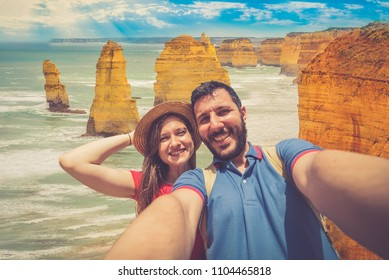 handsome couple backpackers take selfie in front of the cliff of twelve apostles on the ocean of Victoria region in a summer day, Victoria, Australia.
