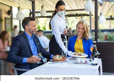 Hermosa pareja almorzando en el restaurante, servida por camarera con una máscara, hora de la corona