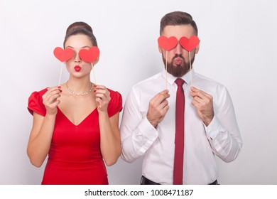 Handsome couple holding decorative sign love, heart symbol. Indoor, studio shot, isolated on gray background