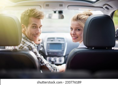 handsome couple looking at camera sitting in a car, view from rear seat