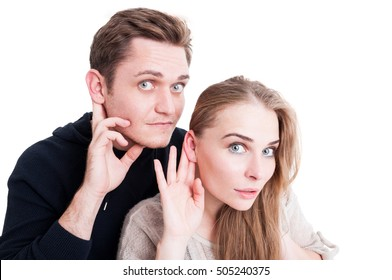 Handsome couple making listening gesture looking amazed isolated on white background with copy text space