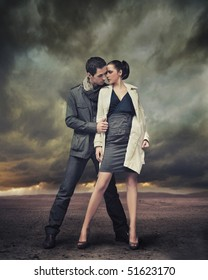 Handsome couple posing over stormy background