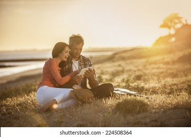 handsome couple sitting on the beach at sunset and using a digital tablet