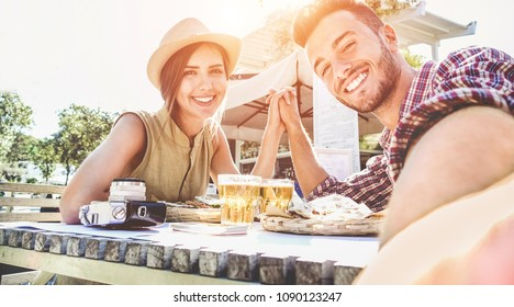 Handsome couple taking selfie with mobile smart phone camera - Young fashion tourist making photo souvenir while eating meal at bar street food restaurant - Vacation, travel lifestyle and love concept