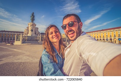 handsome couple tourist take selfie photo with panorama of Praca do Comercio and Statue of King Jose I in Lisbon, Portugal